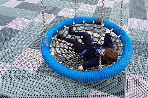 Ein Mädchen in einer Nestschaukel mit Netzgewebe